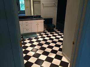 Old bathroom with black and white checkered tiles and blue toilet