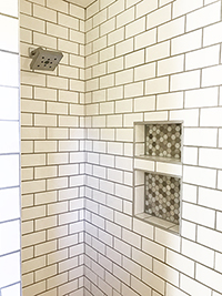 New shower with white subway tile and recessed shelves after master bathroom remodel