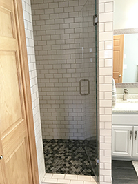 Enclosed shower with white subway tile and glass door after master bathroom remodel