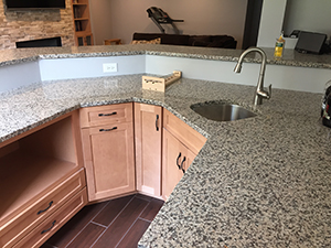 Remodeled kitchen with speckled granite countertop and red ceramic tile in Rochester, MN