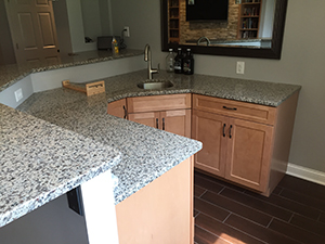 Remodeled basement kitchen with speckled granite countertop in Rochester, MN
