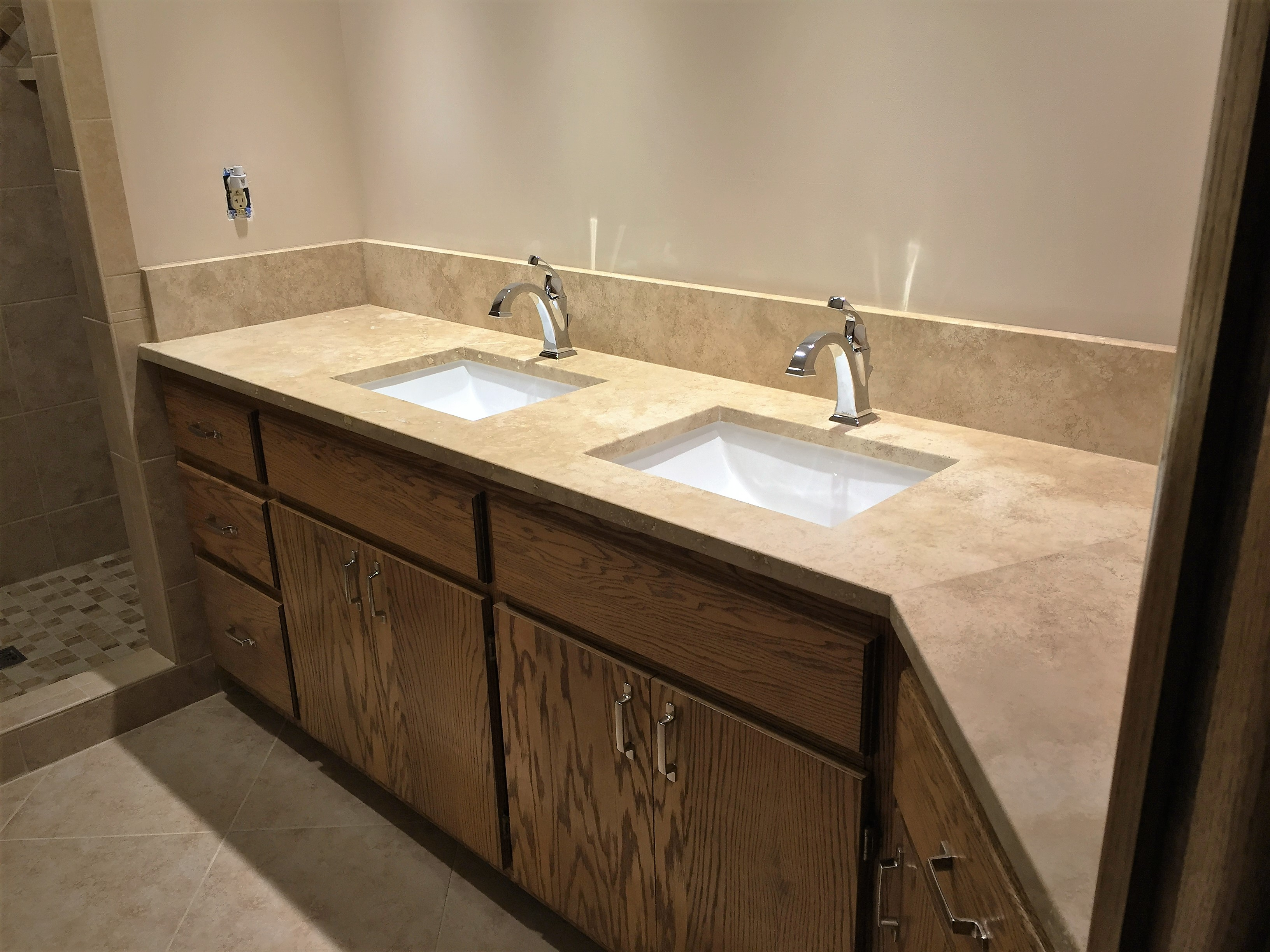 New tan quartz countertop and double sink with chrome fixtures after bathroom remodel