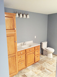 New bathroom build with newly installed cabinetry, vanity, and toilet in Rochester, MN