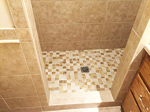 Bathroom shower walls and floor remodeled with large tan porcelain tiles and small mosaic tile in Rochester, MN