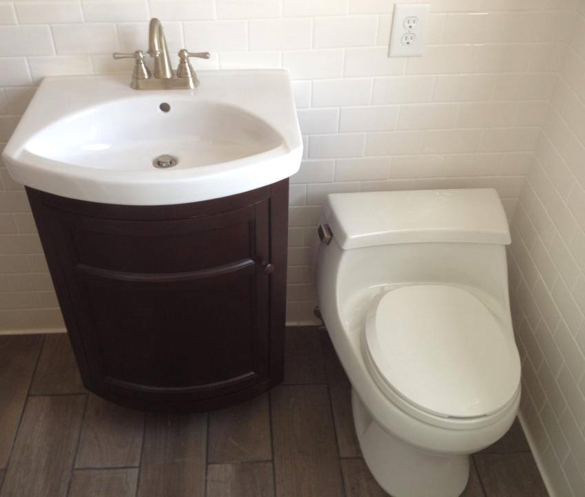 A newly installed white Toto comfort height toilet and simple but elegant vanity